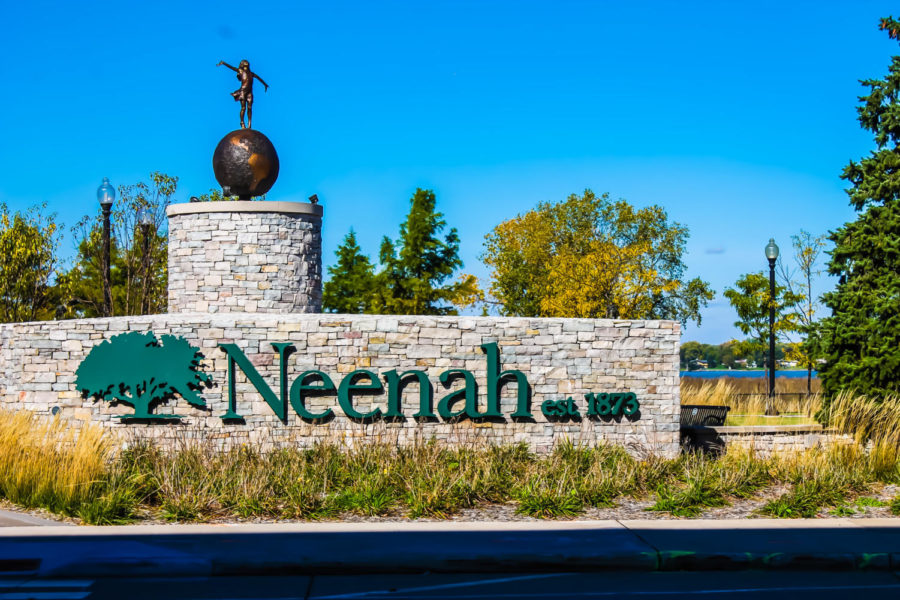 Embracing girl on top of globe; welcoming residents and tourists into downtown Neenah.
