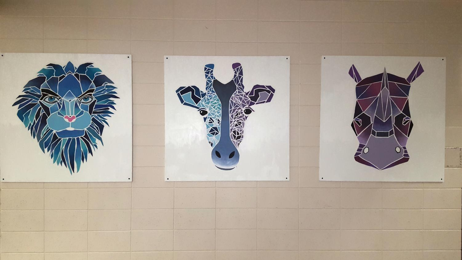 Lion, giraffe and rhino canvases, created by senior Jenna Beyer, greet students outside the cafeteria.