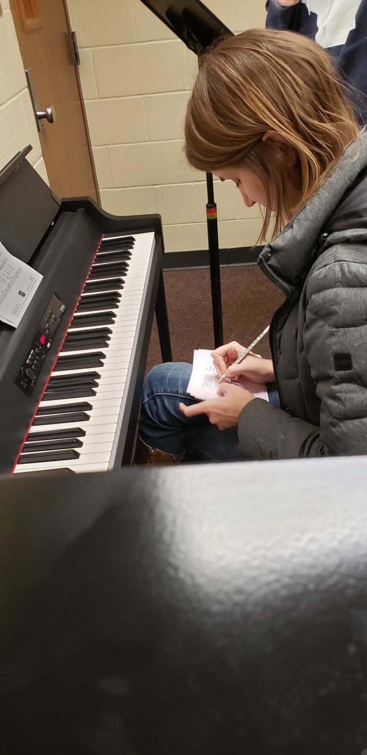 Ms. Amy Westcott makes note of a student's vocal range while auditioning her for Advanced Chamber Choir.