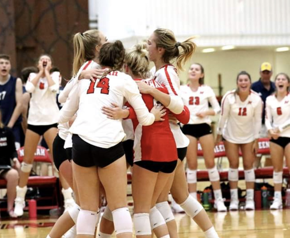 Members of the volleyball  team huddle in support and celebration.