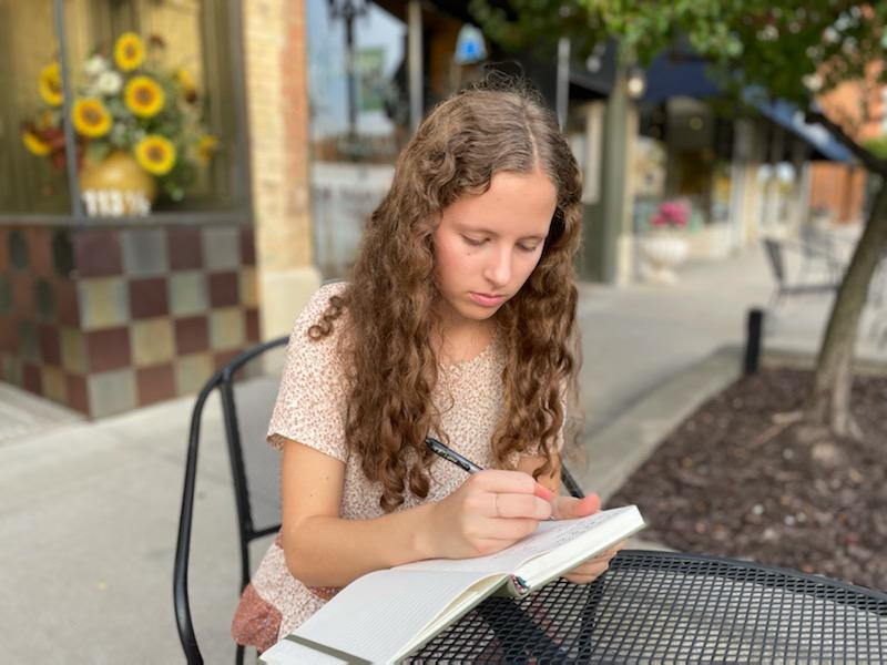 Nestled in a small-town coffee shop, Ashlyn Jacobs, high school senior, expresses her desire to tell the small stories her heart gravitates toward.